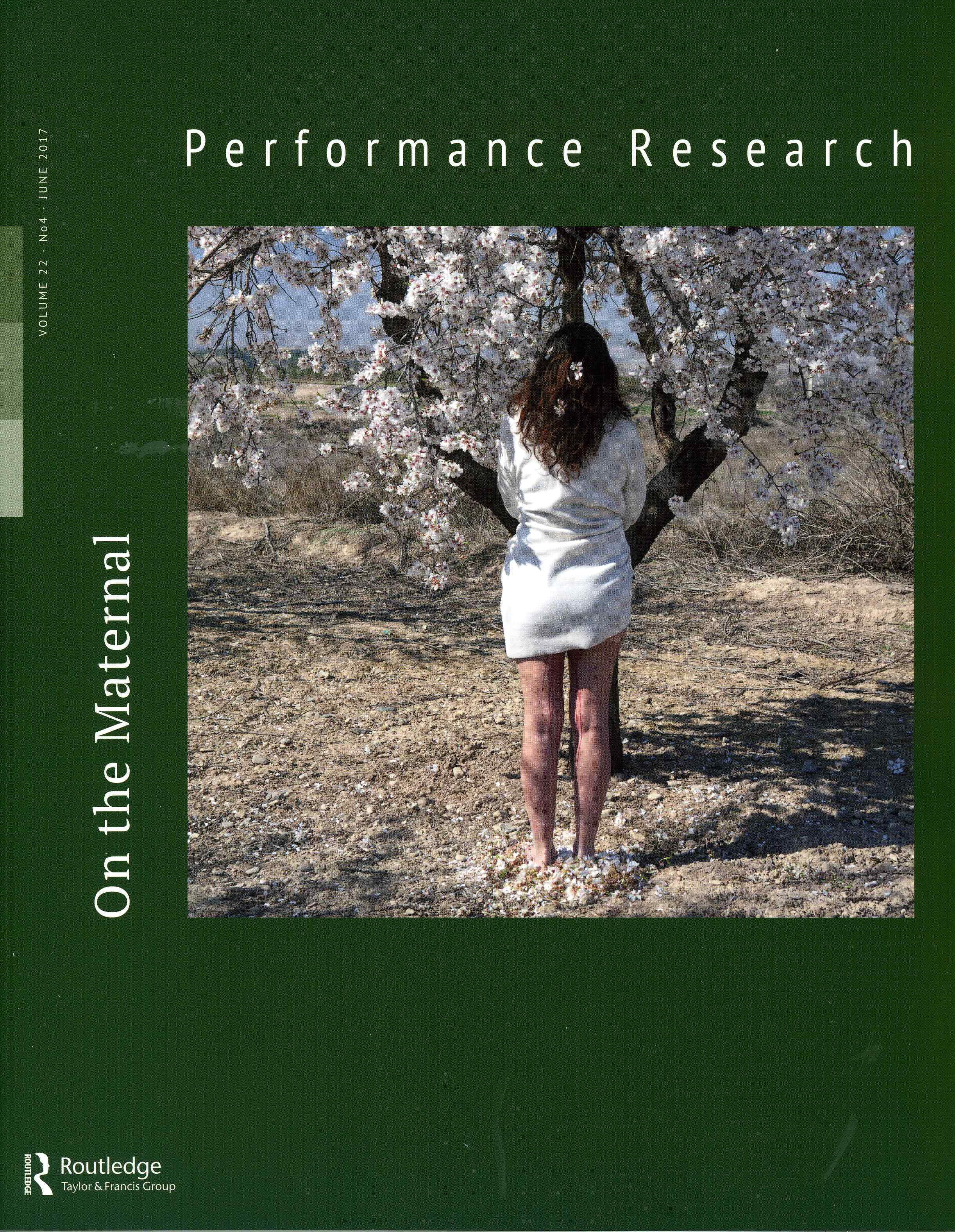 Front cover of the Performance Research journal by Routledge. On the Maternal edition featuring an image of a woman stood under a cherry blossom tree with her back turned wearing a white cardigan and blood dripping down the inside of her legs.