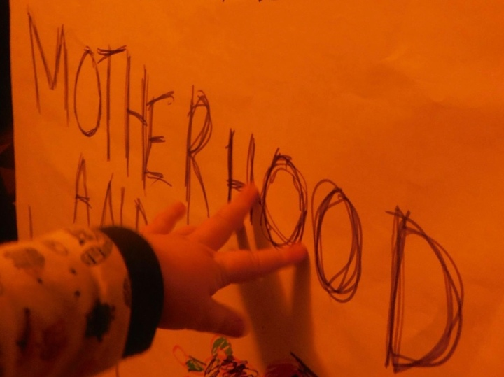 Red image of a child's hand reaching out to touch the handwritten word 'Motherhood'